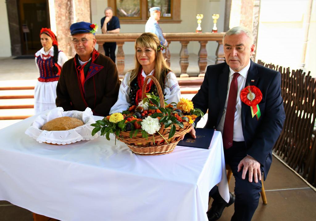 Marszalek-i-starostowie-przy-stole-chleb-dozynkowy-w-koszu-1024x717